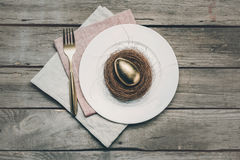 Top view of golden Easter egg in nest on white plate, fork and napkins on wooden table, Stock Photo