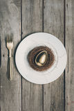 Top view of golden Easter egg in nest on white plate and fork on wooden table, Stock Photo