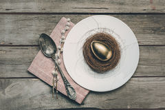 Top view of golden Easter egg in nest on white plate, napkin, catkins and vintage spoon on wooden table Royalty Free Stock Photography
