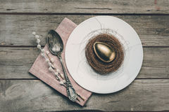 Top view of golden Easter egg in nest on white plate, napkin, catkins and vintage spoon Stock Photo