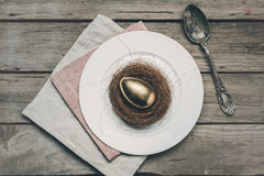 Top view of golden Easter egg in nest on white plate, napkins and vintage spoon on wooden table Royalty Free Stock Photos