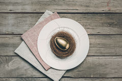 Top view of golden Easter egg in nest on white plate and napkins on wooden table Stock Images