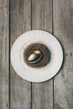 Top view of golden Easter egg in nest on white plate on wooden table Royalty Free Stock Photo