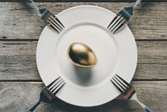Top view of golden Easter egg on white plate and forks on wooden table. Happy Easter concept Stock Photo