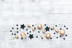 Top view golden Easter eggs over wooden background. Copy space, flat lay Stock Photo