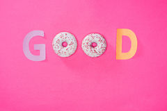 Top view of Good word made from donuts  on pink Stock Photo