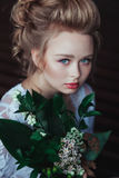 Top view of gorgeous fairytale bride in vin elegant white robe, with flowers bouquet, face closeup Stock Photography