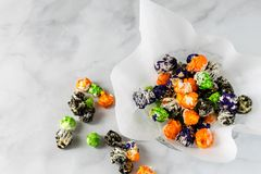 Top view gourmet chocolate covered popcorn. Closeup colorful chocolate covered popcorn in green, orange, black, and purple; useful for party invitations stock photos