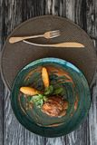 Top view of gourmet ribeye beef steak with basil, fork and knife. On wooden table stock image