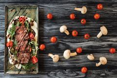Top view of gourmet sliced roasted steak with vegetables. On wooden table stock photo