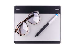 Top view of graphic tablet with pen and retro glass Royalty Free Stock Image