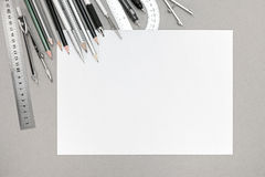 Top view of gray desk with with blank white paper and various dr Stock Photos