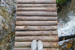 Top view gray sneakers on wooden bridge over river Stock Photos