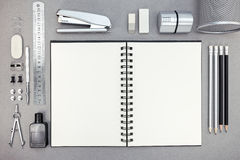 Top view of gray workplace with blank notebook and drawing tools Stock Image