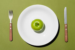 Top view of green apple on white plate with knife and fork on gr Stock Photo