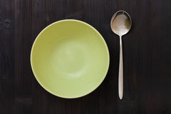 Top view green bowl and spoon on dark brown table Stock Images