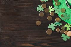 Top view of green hat with golden coins and shamrock on wooden table Stock Photo