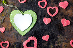Top view of green heart with the pink hearts over black background. Stock Images