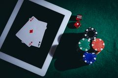 Top view of a green poker table with tablet, chips and dices. Online gambling concept royalty free stock photography