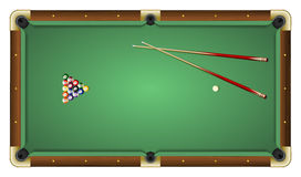 Top view of a green pool table with balls and cues