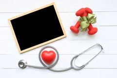 Top view of Green ribbon with dumbells and stethoscope of healthy heart and blackboard on wooden white background, Health care royalty free stock photo