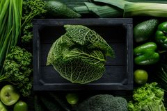 Top view of green savoy cabbage in wooden box between vegetables, healthy. Eating concept royalty free stock photo