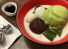 Top view of green tea matcha icecream scoop with red beans mochi and milk in red bowl. Japanese traditional dessert royalty free stock images