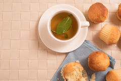Top view of green tea with mint  in a white cup with vanilla muffins. Top view of green tea with mint  in a white cup with vanilla muffins Stock Photography