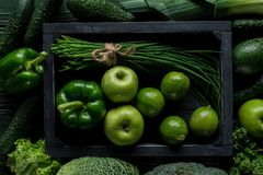 top view of green vegetables and fruits in wooden box on table healthy stock photos