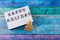 Top view on greeting board with happy holiday wishes and small golden decorative pine tree. On bright blue wooden background Stock Photos