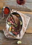 Top view grilled beef meat pan wooden table sauce red wine. Top view grilled beef meat served in frying pan on wooden table with sauce and glass of red wine, top stock image