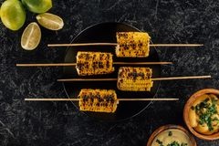Grilled corn pierced with sticks. Top view of grilled corn pierced with sticks on black plate with lime and sauces Royalty Free Stock Image