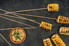 Grilled corn pierced with sticks. Top view of grilled corn pierced with sticks and sauce Royalty Free Stock Photos