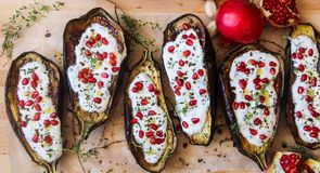 Top view of grilled eggplants and garlic yogurt sauce, garnished wit ruby red pomegranate seeds. And fresh thyme. Mediterranean cuisine and healthy vegetarian royalty free stock images