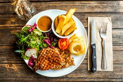 Top view Grilled pork steak with vegetables salad and french fries stock photo