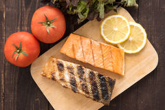Top view grilled salmon on cutting board on wooden background. Stock Photos