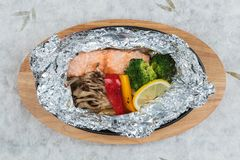 Top view of Grilled Salmon in a Foil Pack with broccoli, bell pepper, mushroom and slice lemon. Top view of Grilled Salmon in a Foil Pack with broccoli, bell Royalty Free Stock Photo