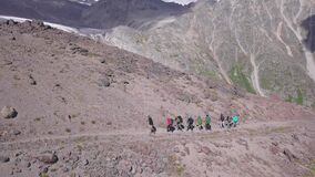 Top view of group of ascending tourists on background of mountain landscape. Clip. Line of climbers follows mountain