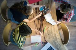 Top view of group of colleagues working in team with reports and laptop royalty free stock photo