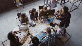Top view of group of mixed race people sitting at table, talking and then start to clapping together. Business meeting. stock footage