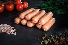 Top view on group of sausages with rucola and tomatoes. Top view on group of raw long thick sausages with pink salt, spices, rucola and tomatoes cherry on black royalty free stock image