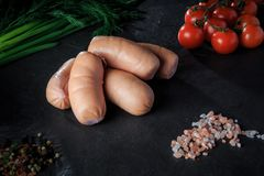 Top view on group of short sausages with dill and tomatoes. Top view on group of thick short sausages with pink salt, spices, green dill and tomatoes cherry on stock image