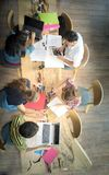 Top view group of teenage friends working in team with reports and laptop. On wooden table Royalty Free Stock Images