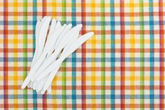 Plastic white knives on a tablecloth Stock Images