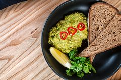 Top view on guacamole with hot pepper, lemon and bread. royalty free stock photos
