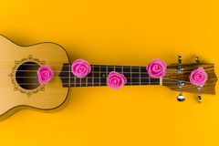 Guitar with rose flowers on the strings lies on vibrant yellow background. Top view of a guitar with rose flowers on the strings lies on  vibrant  yellow stock images