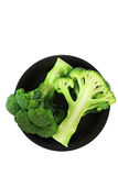 Top view of half of broccoli on black dish over white. Stock Photo