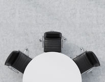 Top view of a half of the conference room. A white round table, three black leather chairs. Office interior. Stock Photos