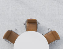 Top view of a half of the conference room. A white round table, three brown leather chairs. Office interior. Stock Photography