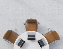 Top view of a half of the conference room. A white round table, three brown leather chairs. Three laptops are on the table. Office Royalty Free Stock Images